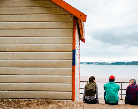 Three people are sat at the beach next to the right hand side of a beach hut facing the sea on a cloudy day.